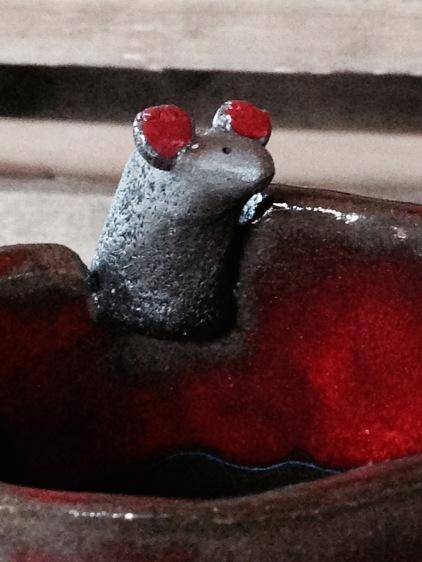 La souris surveille le contenu du bol. Elle semble avoir faim.