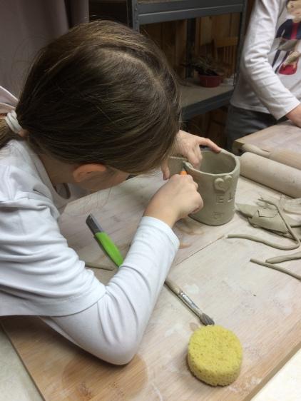 Fabrication d'une tasse lors d'un atelier de poterie enfant